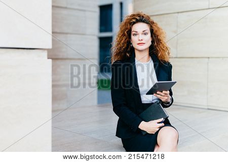 Portrait Of Elegant Lady Dressed In White Blouse, Black Jacket And Skirt, Holding Tablet And Pocket