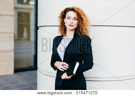 Young Beautiful Woman Wearing Formal Clothes, Dressed Formally, Holding Pocketbook With Pen, Having