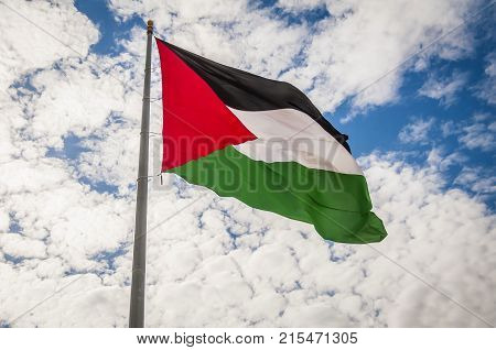 Palestinian flag waving in the sky stock image.