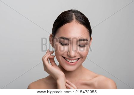 My soft skin. Portrait of joyful gorgeous asian naked woman is touching her hand while looking down and expressing happiness. Skincare and beauty concept. Isolated background