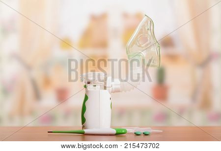 Ultrasonic Nebulizer And An Ampoule With The Solution, Thermometer And Pills On Table