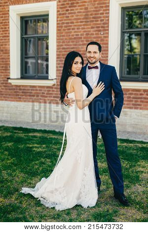 Vertical Portrait Of Attractive Bride And Handsome Bridegroom Stand Close To Each Other, Hug Passion