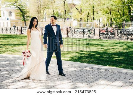 Outdoor Portrit Of Lovely Married Couple Walk Together, Keep Hands Together, Enjoy Nice Weather. Smi