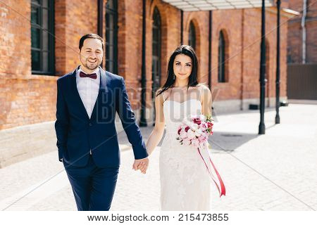 Bearded Male Bridegroom Wears Formal Black Suit Keeps His Bride`s Hand, Has Happy Expression, Celebr