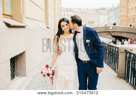 Affectionate Handsome Bridegroom With Beard Kisses His Future Wife. Lovely Brunette Bride Wears Nice
