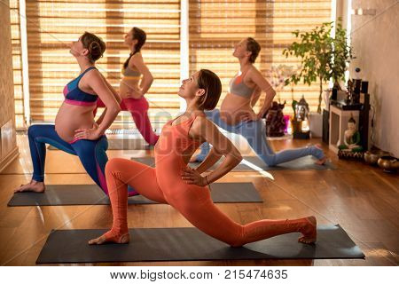 Relaxed impregnate ladies repeating exercise after instructor. They kneeing on one leg, putting hands on small of back and looking up with smile. Profile