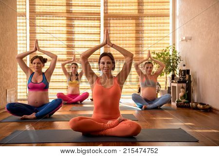 Happy impregnate women on yoga-lesson sitting on carpets and rising hands up. they looking at camera with smile. portrait
