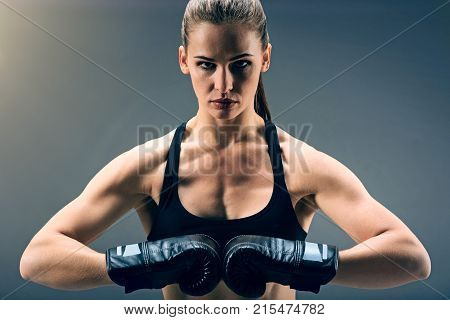 Stand up and fight. Focused sporty girl looking into the camera confidently while standing with her hands in boxing gloves joint together.