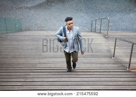 Inquisitive Hispanic intern moving up stairs outdoors and looking around. Pensive handsome student with satchel going to university. First day of work concept