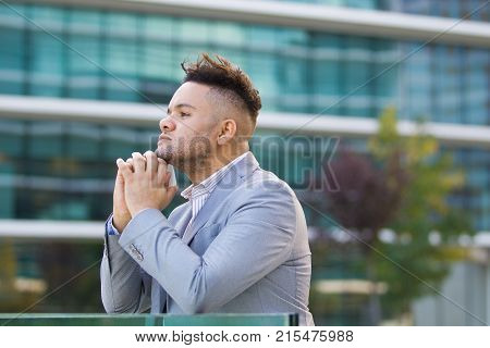 Pensive successful businessman walking in city. Contemplative young man reflecting about career. Handsome male manager holding smartphone and leaning on railing. Deep in thoughts concept