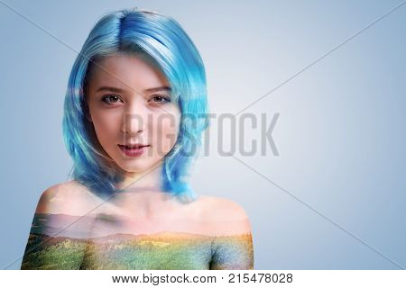 Wistful look. Interested millennial girl standing over the background and looking into the camera dreamily while posing alone.