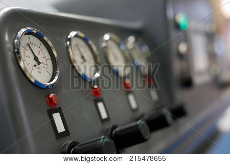 Analog manometers on a control panel of industrial machine. Selective focus.