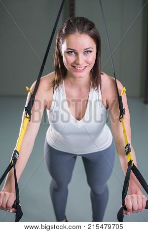 Young woman doing suspension training push-ups with trx fitness straps