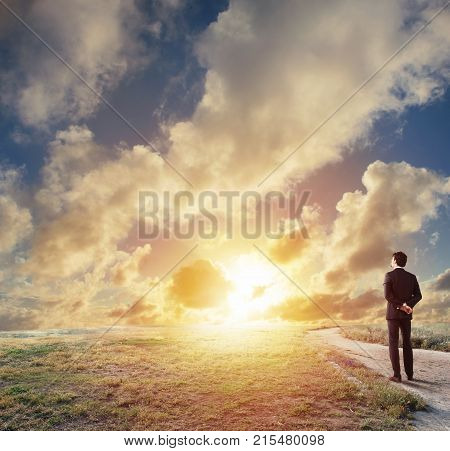 Businessman looks far during sunrise. Future and new business opportunity concept
