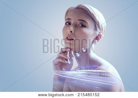 Unearthly beauty. Attractive millennial girl resting her chin on a hand while looking into the camera confidently and posing against the urban background.