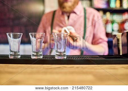 Mid section of unrecognizable bartender cleaning glasses at bar counter row of little empty shots in row in foreground