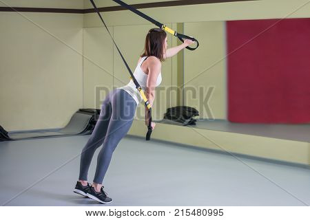 Young woman doing suspension training push-ups with trx fitness straps, side view.