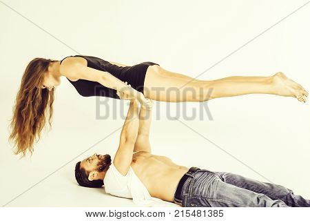 bearded man brutal caucasian hipster with beard and strong muscular body and pretty girl or sexy fit woman with long brunette hair in black undershirt do yoga acrobatic balance isolated on white