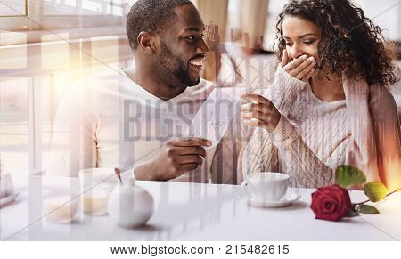 Planning future travel. Close up of young positive man showing flight tickets while his girlfriend covering her face and expressing surprise
