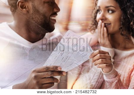 Surprise. Close up of young positive man presenting flight tickets and showing delight while his girlfriend covering her mouth with a hand and being pleased