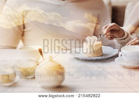 Pleasant date. Close up of tasty cheese cake lying on the plate while young girl using a fork and cutting it
