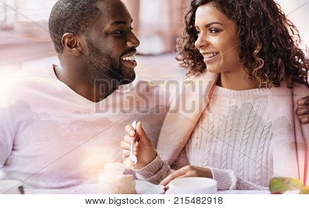 Try this cake. Close up of young smiling couple sitting in the cafe while looking at each in the eyes and showing true feelings