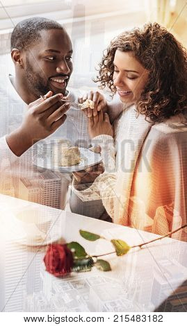 Positive day. Young pleasant couple sitting in the cafe while enjoying tasty cake and showing bright emotions
