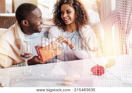 Lovely present. Young smiling couple looking at each other while holding a present and showing love and concern