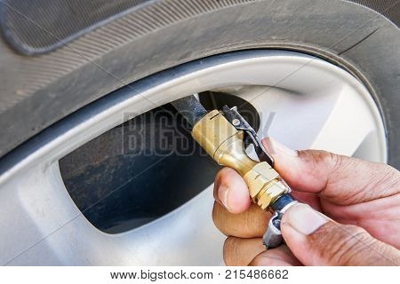 Checking tire pressure. Pumping air filling air into a car tire.