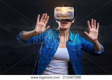 Emerging in VR. Glad pleasant young woman holding her hands up and opening her mouth while posing against grey background