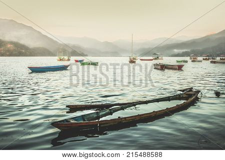 Colorful boats on Phewa lake at sunset. Sunk boat on the foreground.