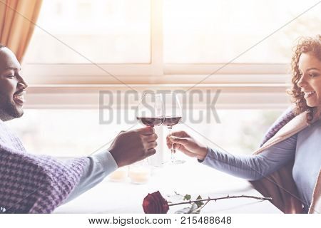 Our appointment. Smiling black man sitting in semi position holding bocal with wine in right hand while having date with his sweetheart