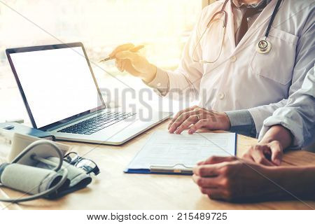 Doctor Consulting With Patient Presenting Results On Blank Screen Tablet Computer Sitting At Table