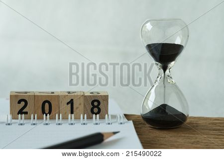 New year 2018 goals target or checklist concept as sandglass and white paper note with pencil and number 2018 wooden cube block.