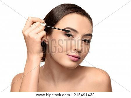 Beautiful young woman with eyelash extensions applying mascara, on white background