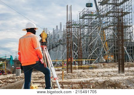 Surveyor Builder Engineer With Theodolite Transit Equipment At Construction Site Outdoors During Sur