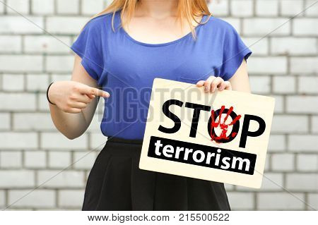 stop terrorism concept. girl on a brick wall background. hand pointing to a wooden sign