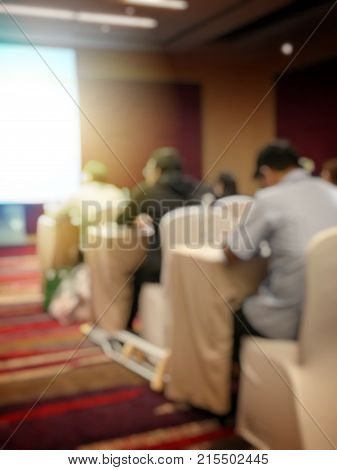 Abstract blurred image of people sitting in conference room for profession seminar with attendee presenter and audience background business & educaction concept official new product launches