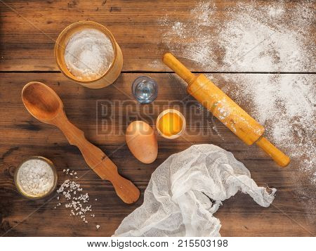 Spilled flour, salt, egg yolk, fabric, wooden spoon and rolling pin. Still life on the background of the old wooden table, top view in rustic style with kitchen utensils.