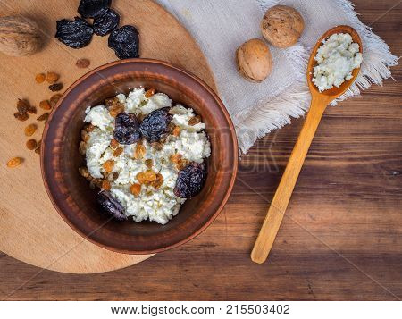 Clay bowl with cottage cheese, raisins and dried apricots next to the wooden spoon and walnuts. Dairy product cottage cheese in bowl on old wood table. Template for menu or print design, top view.