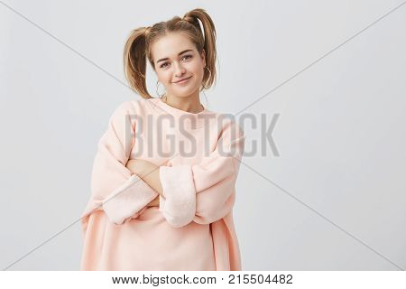 Stylish, trendy, pretty girl in pink long-sleeved sweatshirt with two ponytails and big round earing posing against gray background, keeping her arms folded. Pretty girl smiling, expressing positive emotions.