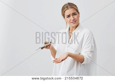 Studio portrait of puzzled or anxious pretty girl with blonde hair frowning her face looking at phone seeing bad news or photos posing against gray background. Negative human emotion, reaction, expression.