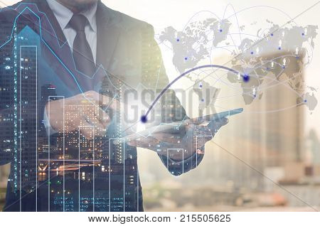 Double exposure of businessman using tablet for connection with cityscape and financial graph on blurred building background Business Trading concept Elements of this image furnished