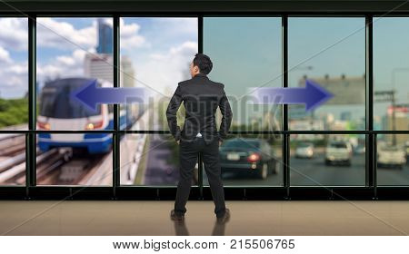 Businessman standing in doubtthinking the two different choices of transportation for traffic jam with rush hour which indicated by arrows pointing in opposite direction business decision concept