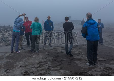 Kamchatka Peninsula, Russia - August 26, 2016: Group of tourists in the fog of the volcano caldera Gorely. Kamchatka Peninsula.