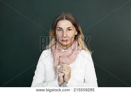 Isolated shot of attractive confident European middle aged lady wearing elegant clothes posing at studio wall with hands clasped having pensive deep in thoughts facial expression. Body language