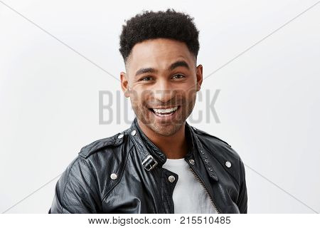 Close up portrait of young cheerful dark-skinned american man with curly hair in white t-shirt and leather jacket smiling brightly, looking in camera with happy and excited face expression