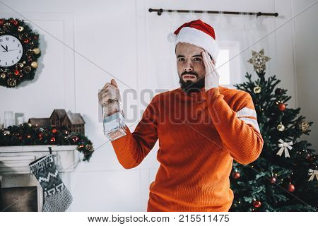 A picture of guy standing in a white and bright room and holding an empty bottle in one hand keeping the other hand close to the head. Las night he had a Christmas party with his friends and drank too much alcohol so now he has a hangover. Cut view