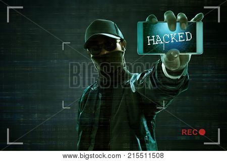 Unknown hacker holding mobile phone to hacked
