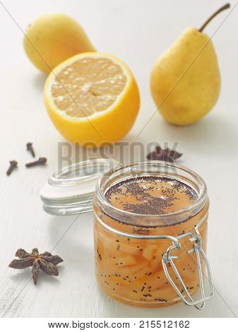 Jam with pear and poppy seeds in a glass jar upon white wooden table. Vertical. Selective focus on the jar.